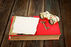 Vintage binoculars on red ancient book with blank page for text. nostalgic vintage background. Vintage binoculars on red ancient book with blank page. nostalgic Stock Image