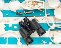 Vintage binoculars, shells, small fishing boat and sailor rope on a wooden background. Sea concept. Overhead view. Stock Photo