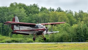 Vintage biplane landing above runway stock photography