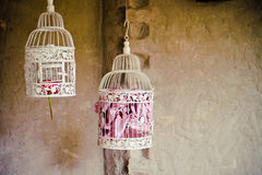Vintage bird cages. Ivory color antique/vintage bird cages used for outdoor decoration, suspended from the ceiling at a wedding.  Each one consisting a pink Stock Photography