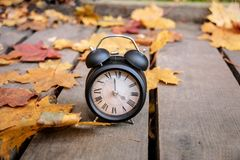 Vintage black alarm clock on autumn leaves. Time change abstract photo. stock photography