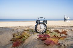 Vintage black alarm clock on autumn leaves. Time change abstract photo. royalty free stock photography