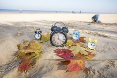 Vintage black alarm clock on autumn leaves. Time change abstract photo royalty free stock image