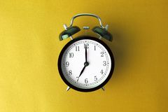 Vintage black alarm clock on yellow color background Stock Photography