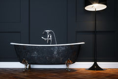 Vintage black bathtub with silver legs in antique interior with Royalty Free Stock Photo