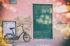 Vintage Black Bicycle Bike against Pink Stucco House with Green Door in Italy. A vintage Black Bicycle Bike leans against a Pink Stucco House with Green Door in Stock Images