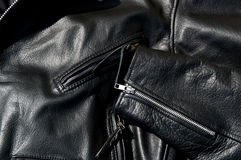 Vintage black cowhide leather motorcycle jacket. High contrast close up of black leather motorcycle jacket showing zippered pockets and portion of  sleeve in Stock Photography