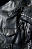 Vintage black leather motorcycle jacket. High contrast close up of black leather motorcycle jacket showing zippered pockets and coin pocket with snap button and Stock Image