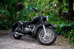 Vintage black motorcycle in tropical setting Royalty Free Stock Images