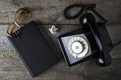Vintage black phone, old glasses and notebook Stock Photography