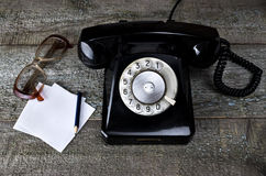 Vintage black phone and old glasses Stock Photography