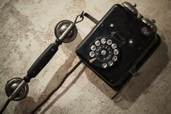 Vintage black phone on old gray concrete wall Stock Image