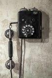 Vintage black phone on old gray wall. Vintage black phone hanging on old gray concrete wall Stock Photos