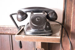 Vintage black phone on old wooden table Stock Photos