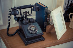 Vintage black phone on old wooden table Royalty Free Stock Image