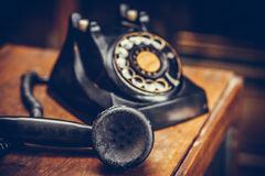Vintage black phone on old wooden table background. Selective focus Royalty Free Stock Photography