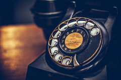 Vintage black phone on old wooden table background. Selective focus Royalty Free Stock Image