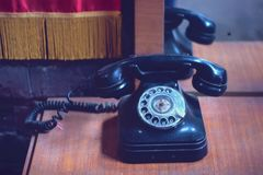 Vintage black phone on old wooden table. Background Stock Photos