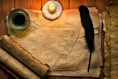 Vintage feather with paper and ink on table in light of candle. Vintage black quill pen and candle on old blank paper sheet Stock Images