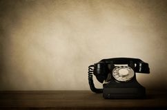 Vintage Black Telephone with Aged Effects on Wooden Desk Royalty Free Stock Photos