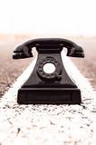 Vintage Black Telephone. On the Aphalt Road Royalty Free Stock Photos