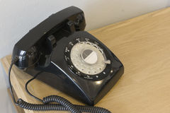 Vintage black telephone on wooden table. Vintage black telephone on wooden table in room Stock Image