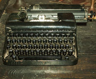 Vintage black typewriter. On an old wooden table Stock Image