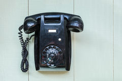 Vintage black wall telephone. Vintage black bakelite telephone hanging on a green wooden wall Stock Photography