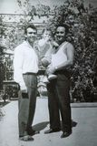 Vintage black and white photo of brothers holding a child, family, 1950s European. Vintage black and white photo of brothers holding a child. Family, young stock images