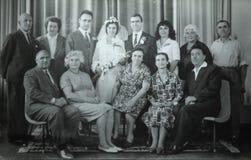 Vintage black and white photo of family wedding, 1950s European. Vintage black and white photo of men and women at family wedding with bride holding flowers royalty free stock photos