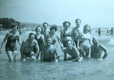 Vintage black and white photo of men and women in the sea, 1950s European. Vintage black and white photo of men and women in the sea wearing swimming costumes royalty free stock photo