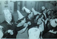 Vintage black and white photo of people at a party dancing and wearing funny hat, Christmas Party? 1950s European. Vintage black and white photo of people at a stock photo