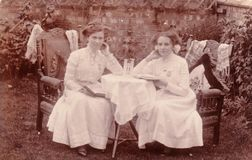 Vintage black and white photo postcard of two women sitting at table in garden 1920s?. Two women sat in garden holding books. 1920s fashion social history royalty free stock images