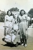 Vintage black and white photo of sisters with a child in pram, family, 1950s European. Vintage black and white photo of sisters with a child in pram. Family royalty free stock photography