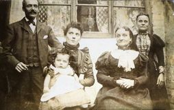 Vintage black and white photo of a Victorian family in front of house 1880s - 1900s. Victorian fashion, social history royalty free stock photo