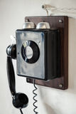 Vintage black wired phone on the wall Stock Image