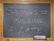 Vintage blackboard chalk financial message. The grungy scratched and filthy blackboard displays a printed message in chalk.  The concept of savings equals Stock Photography