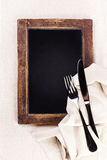 Vintage blackboard with wooden frame with linen towel and servin Royalty Free Stock Images