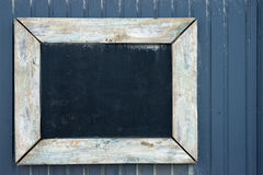 Vintage blackboard on a wooden wall. Copy space on a vintage blackboard to write your own text Stock Photo