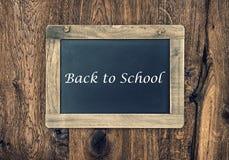 Vintage blackboard on wooden wall. Back to School Stock Image