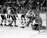 Vintage Blackhawks and Bruins battle in front of the Hawks goal. Chicago Blackhawks goalie Tony Esposito (35) makes a save on Boston Bruins forward Wayne royalty free stock image