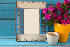 Vintage blank frame, cup of coffee next to beautiful purple mediterranean summer flowers.  template, ready to put photography Stock Images