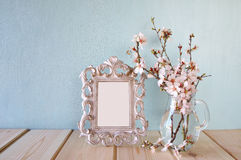 Vintage blank frame next to white spring flowers. selective focus. template, ready to put photography Stock Photos