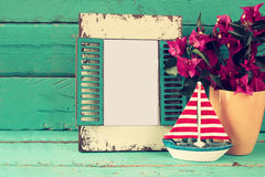 Vintage blank frame, sailboat next to beautiful purple mediterranean summer flowers. vintage filtered image Royalty Free Stock Images