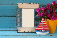 Vintage blank frame, sailboat next to beautiful purple mediterranean summer flowers. vintage filtered image Royalty Free Stock Photos