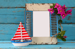Vintage blank frame, sailboat next to beautiful purple mediterranean summer flowers. vintage filtered image Stock Image