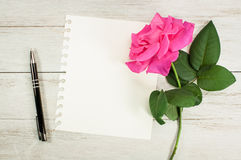 Vintage : Blank old photo. Blank old photo near pink rose and pen on wooden background Stock Photography