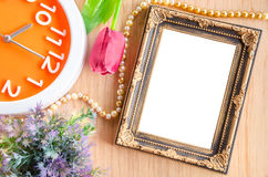 Vintage blank photo frame and clock with flower on wooden backgr Royalty Free Stock Image