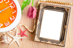 Vintage blank photo frame and clock with flower. Royalty Free Stock Image