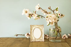 Vintage blank photo frame next to spring flowers Stock Photography